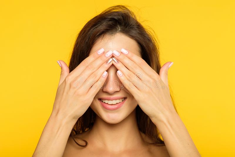 掩藏寻求微笑的快乐的女孩覆盖物眼睛手 免版税库存图片