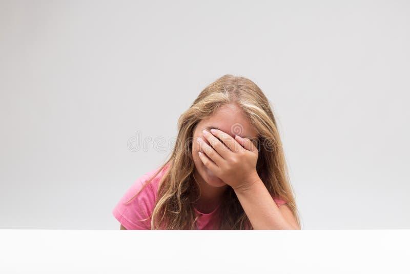 掩藏的小女孩在她的手后 免版税库存图片