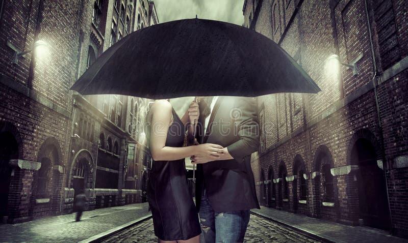 掩藏的年轻夫妇在伞下 免版税库存照片