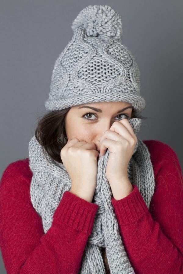 掩藏的年轻逗人喜爱的少年在她轻松的冬天围巾 库存图片