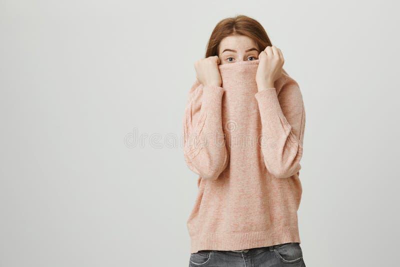 掩藏面孔在引体向上和看与被举的眼眉的一个逗人喜爱的姜女孩的画象照相机,站立反对a 免版税库存图片