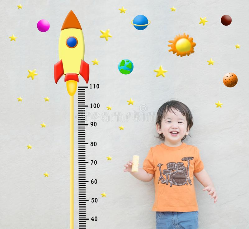 措施高度的特写镜头愉快的亚洲孩子立场与在大理石石墙的逗人喜爱的动画片构造了在孩子c成长的背景  库存照片