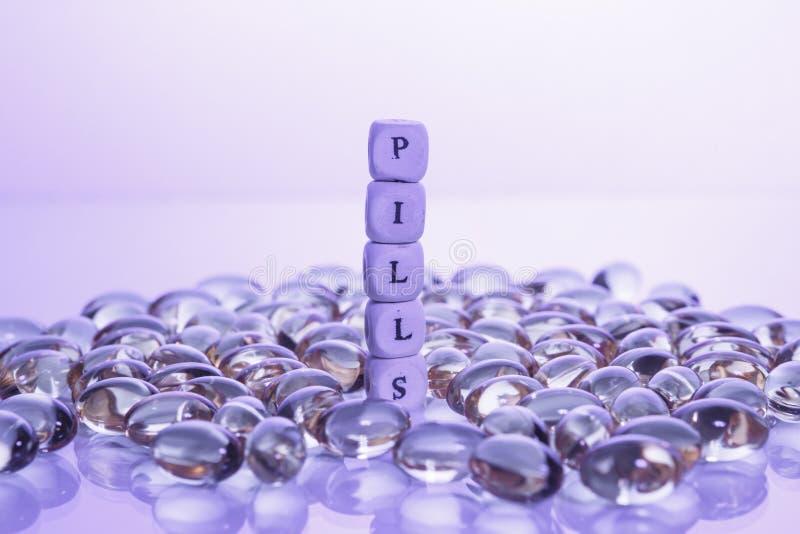 措辞从立方体和卵磷脂胶凝体药片信件的药片在轻的背景的 库存照片