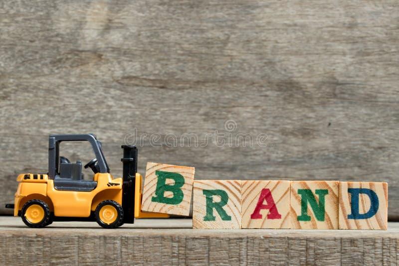 措辞品牌的黄色塑料铲车举行信件B 库存图片