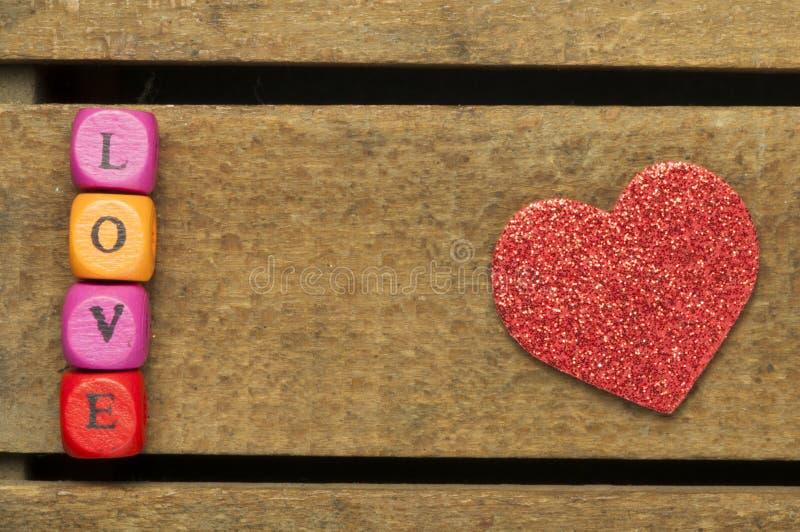 措辞在多彩多姿的木立方体的爱在木背景 免版税库存图片
