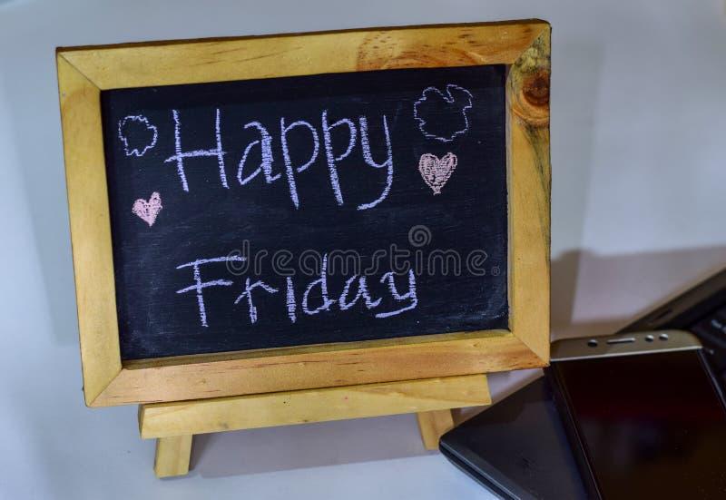 措辞在它和智能手机,膝上型计算机的一个黑板写的愉快的星期三 库存图片