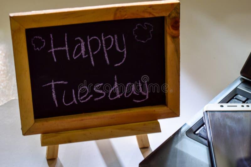 措辞在它和智能手机,膝上型计算机的一个黑板写的愉快的星期二 图库摄影