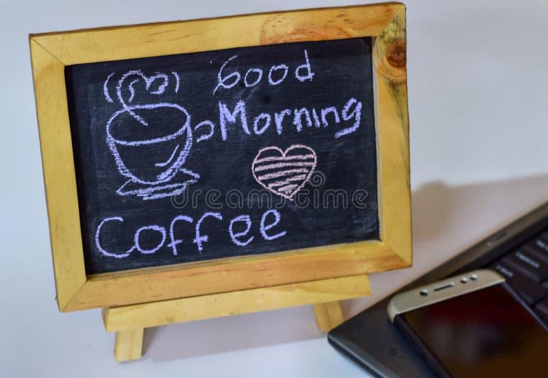 措辞在它和智能手机,膝上型计算机的一个黑板写的早晨好咖啡 库存图片
