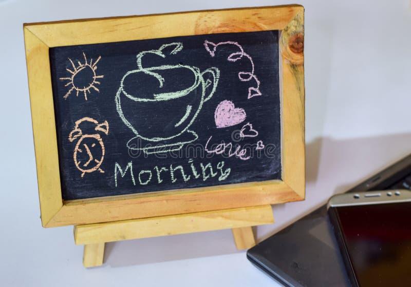 措辞在它和智能手机,膝上型计算机的一个黑板写的早晨好咖啡 库存照片