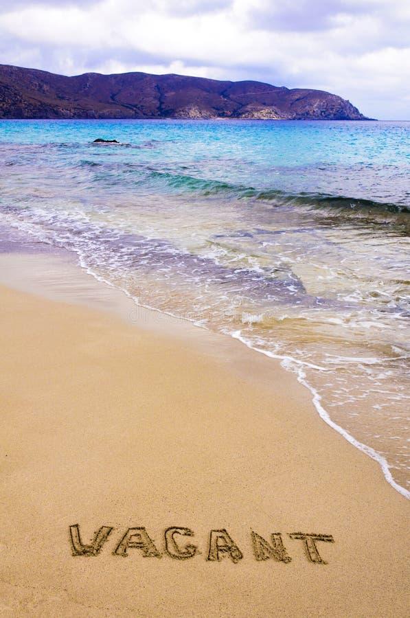 措辞在沙子写的空置,在一个美丽的海滩 图库摄影