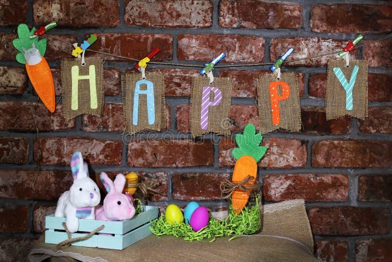 措辞愉快在垂悬在一条线的麻袋布标记用橙色红萝卜、五颜六色的复活节彩蛋,玻璃瓶子和复活节兔子兔子 免版税库存照片