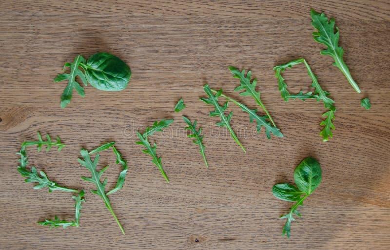 措辞春天由rucola和菠菜叶子制成在木桌 图库摄影