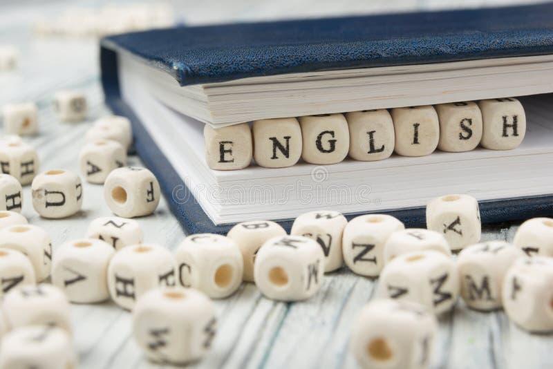 措辞用块木信件做的英语在堆在木桌的其他信件旁边 图库摄影