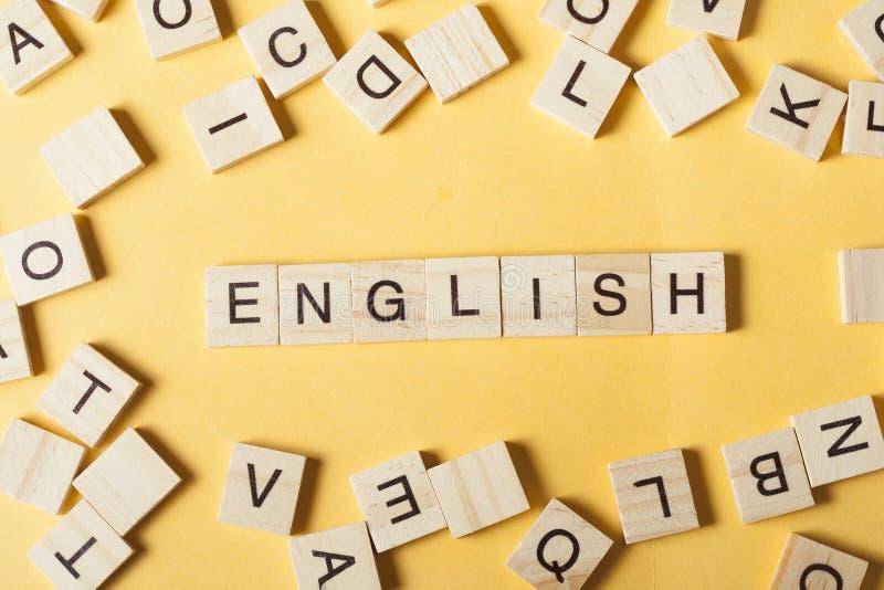 措辞用块木信件做的英语在堆在木桌的其他信件旁边 免版税库存照片