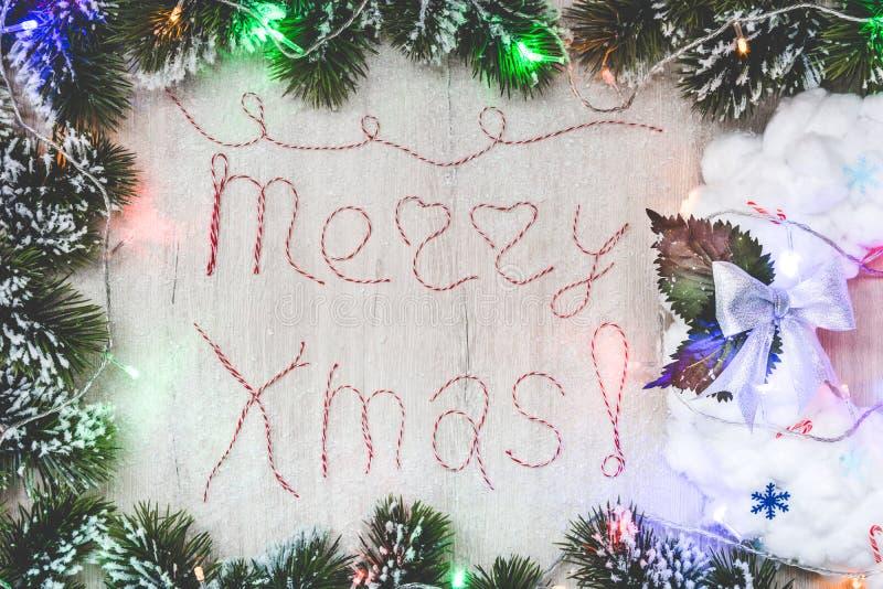 措辞由红色和白色螺纹做的圣诞快乐在木背景 库存图片
