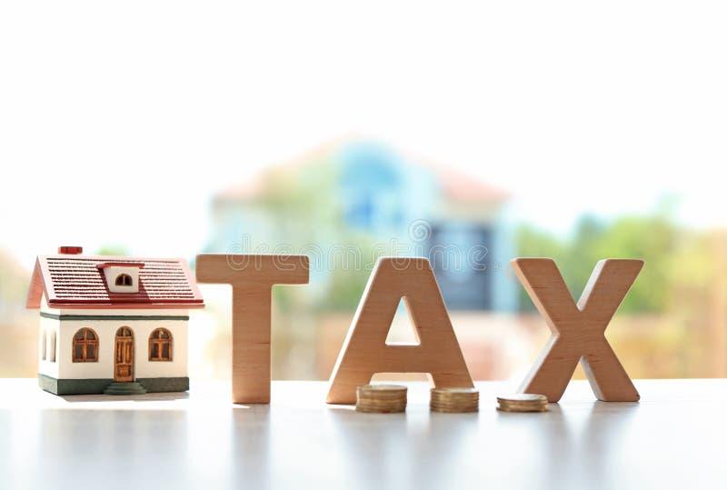 措辞税、房子模型和硬币在桌上 免版税库存照片