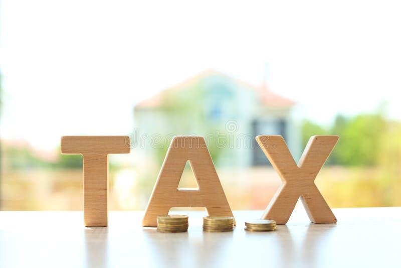 措辞税和硬币在桌上反对弄脏 免版税图库摄影