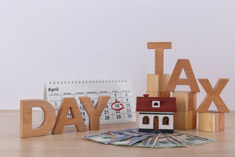 措辞税天、木立方体、房子模型、日历和金钱在桌上反对轻的背景 免版税库存照片