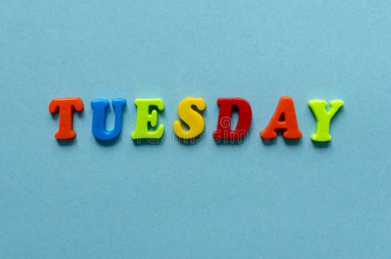 措辞`色的塑料磁性信件星期二`在蓝纸背景的 免版税图库摄影