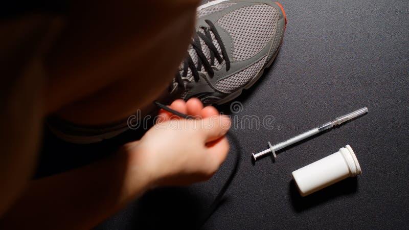 掺杂:运动员穿戴鞋子并且采取药片 库存图片