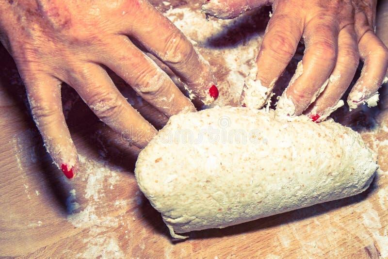 揉和按摩家制面包面团的端庄的妇女手 库存照片