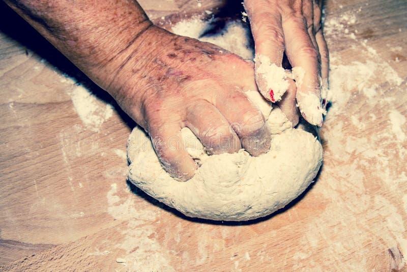 揉和按摩家制面包面团的端庄的妇女手 免版税库存照片
