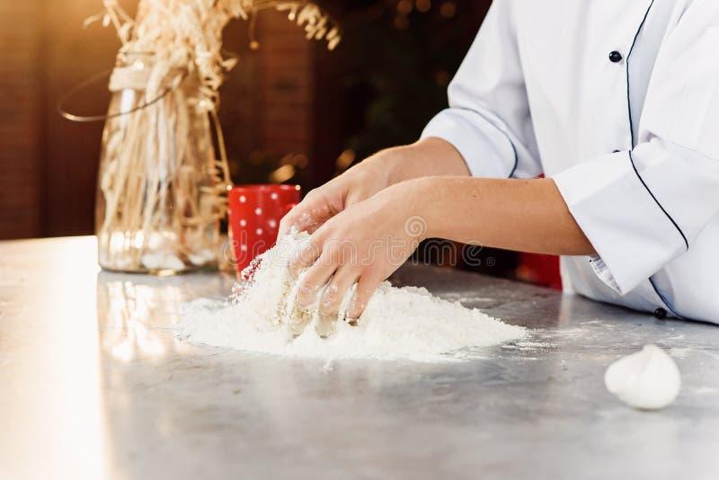 揉在桌上的女性面包师的手面团用面粉,鸡蛋 免版税库存照片