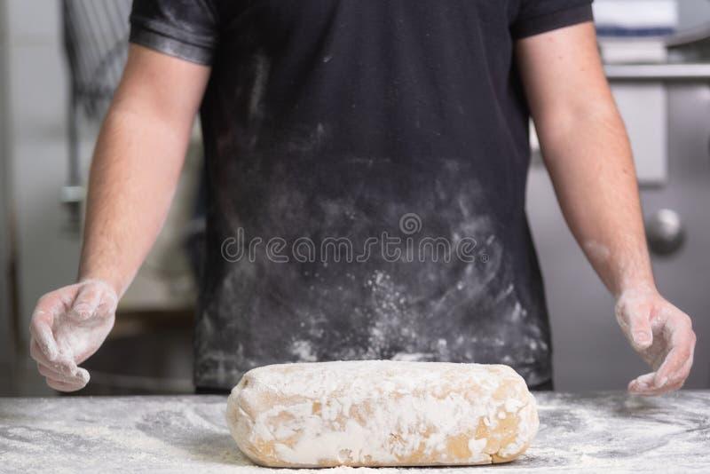 揉新鲜的未加工的面团的贝克在面包店 免版税库存照片