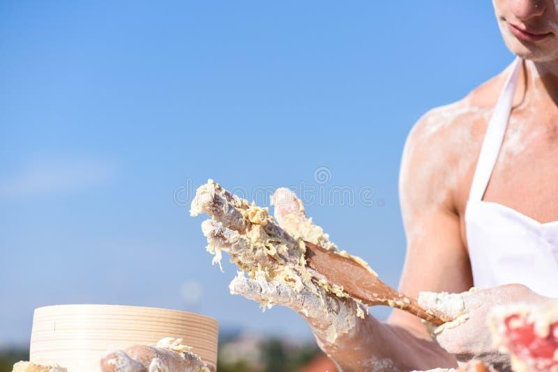 揉未加工的稠粘的面团的肌肉面包师或厨师的手 厨师的手烹调与稠粘的面团和面粉一起使用 库存图片