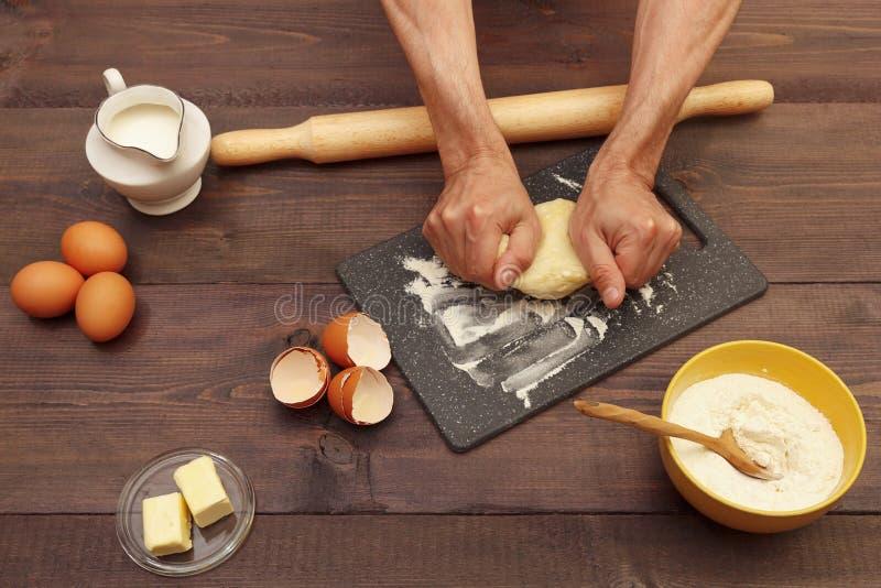揉烘烤的贝克手面团在木桌上的委员会 库存照片