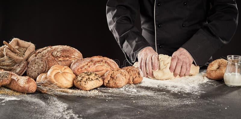 揉烘烤的面包的贝克新鲜的面团 库存图片