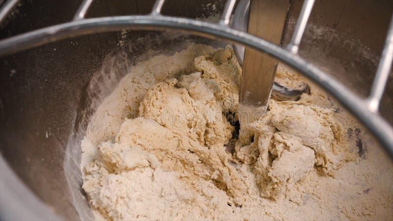 揉的面团特写镜头在生产搅拌器的 E 螺旋捏制机在面包店揉烘烤的新鲜的面团 免版税库存照片