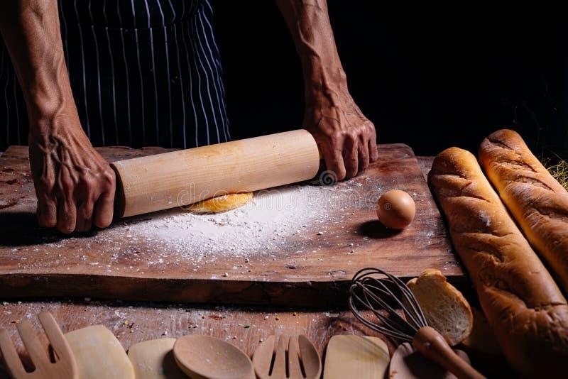 揉面包店的厨师手面团 做由男性手的面团在面包店 人揉的面团关闭  看见的强的手 免版税库存图片