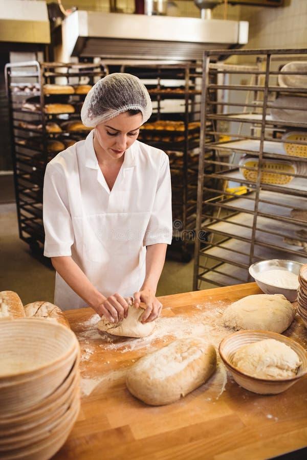 揉面团的女性面包师 免版税库存图片