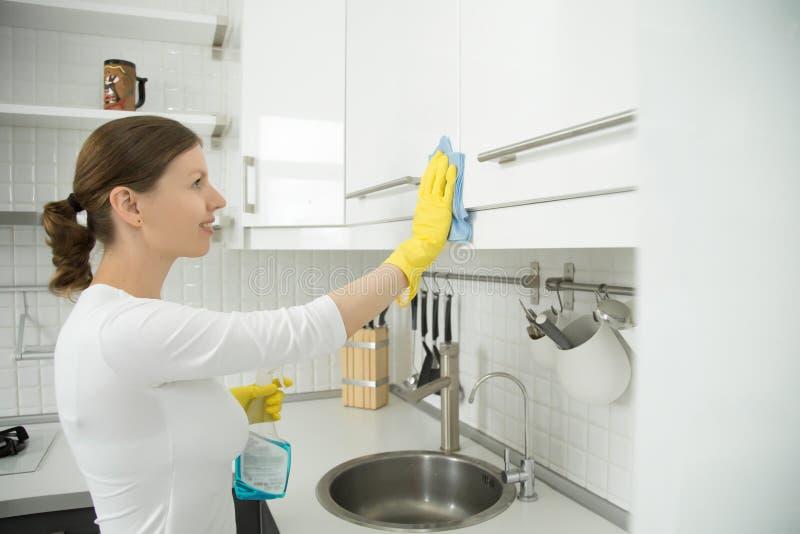 描出可爱的妇女清洗的白色厨房clos画象  免版税库存照片