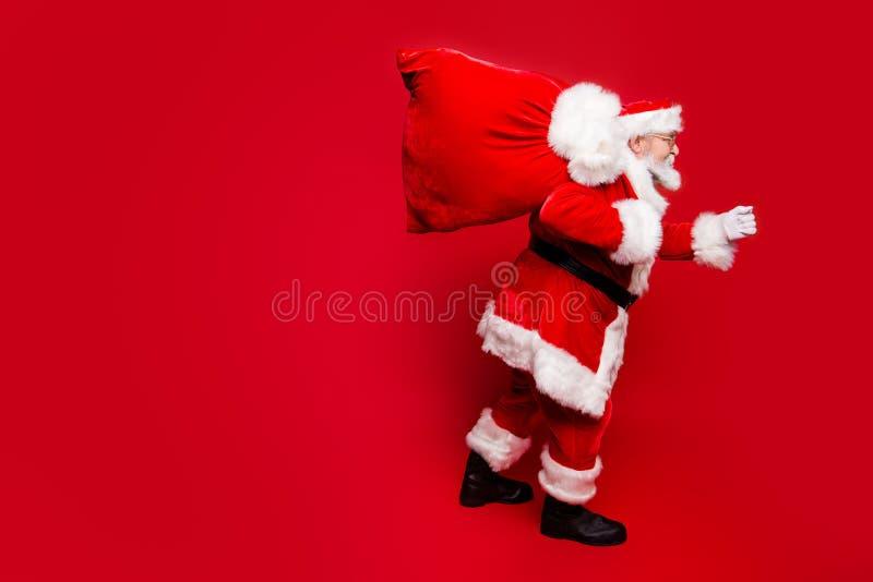 描出圣诞老人侧视图在镜片手套成套装备的在仓促 免版税库存图片