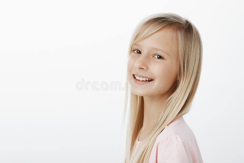 描出快乐地微笑满意的愉快的矮小的白种人女孩的射击有长的金发的,转动在照相机和 库存照片