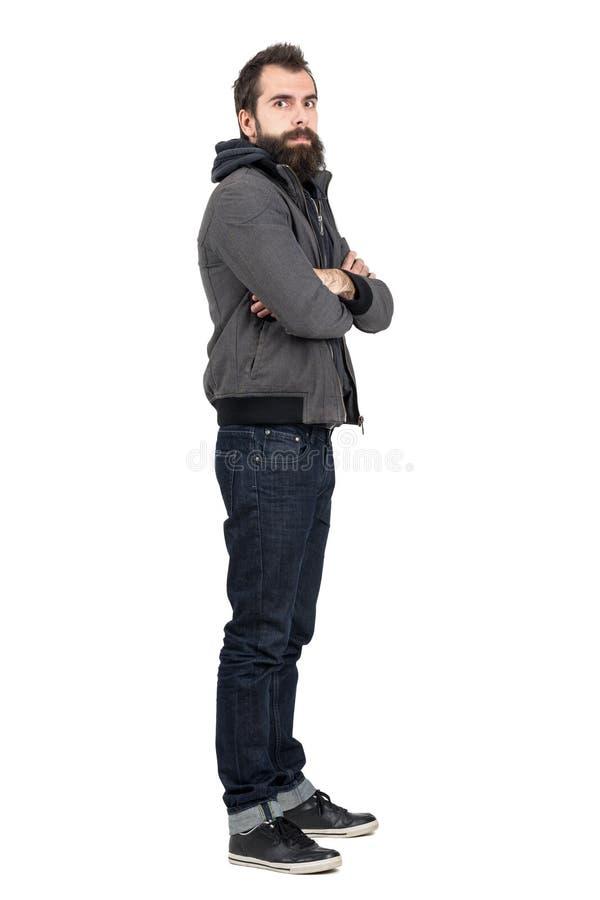描出有胡子的在戴头巾运动衫的人佩带的夹克看法有看照相机的横渡的胳膊的 免版税库存图片