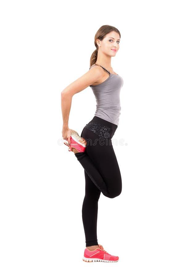 描出舒展腿的年轻运动的女性秀丽侧视图  免版税库存图片