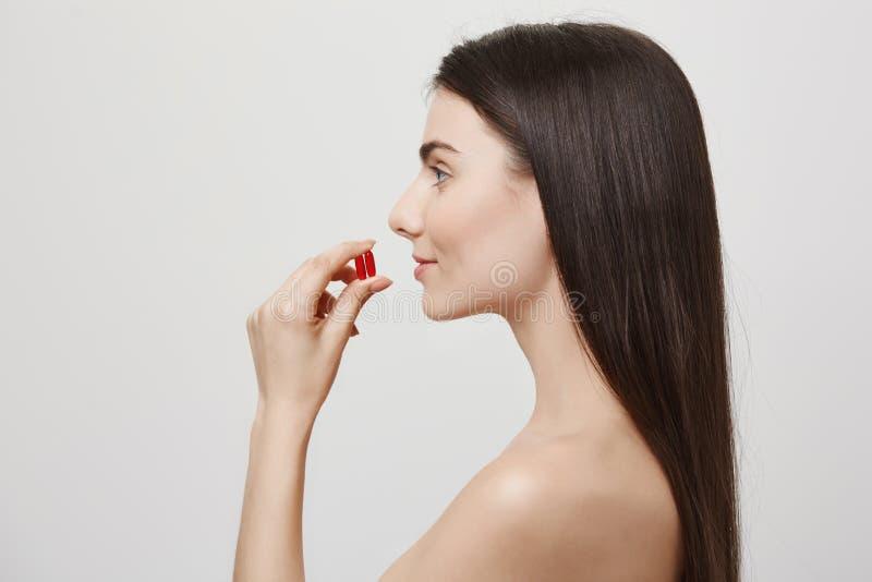 描出采取医学或维生素的可爱的健康欧洲妇女画象,拿着两个药片在嘴附近和 免版税库存照片