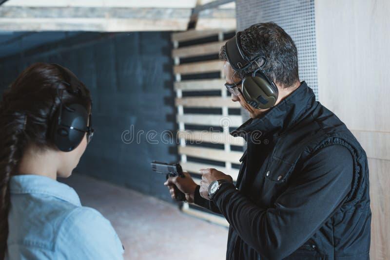 描述手枪的男性辅导员背面图对女性客户 免版税库存图片