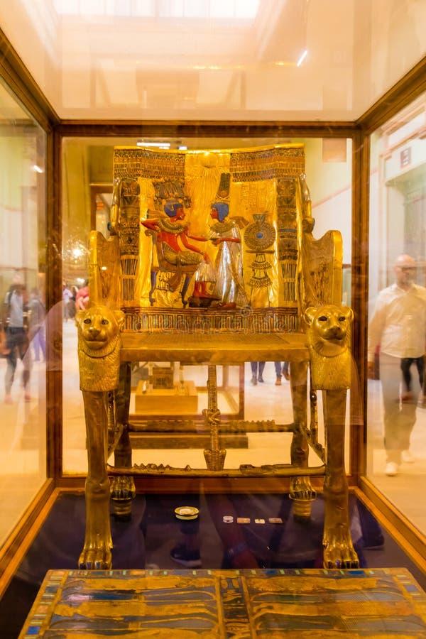 描述法老王和他的妻子安克姗海娜曼的Tutankhamun金黄王位 免版税库存图片