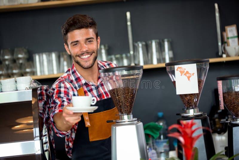 提供一杯咖啡的英俊的侍者 图库摄影