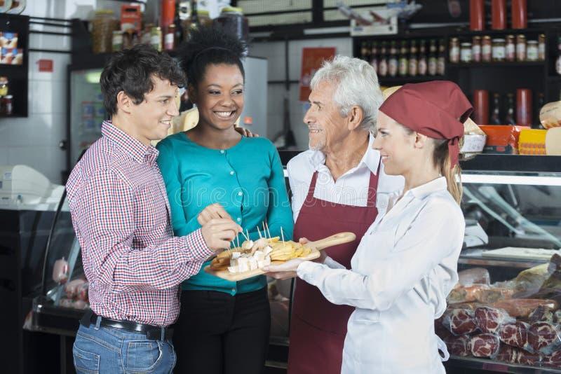 提供乳酪样品的推销员为顾客在商店 免版税图库摄影