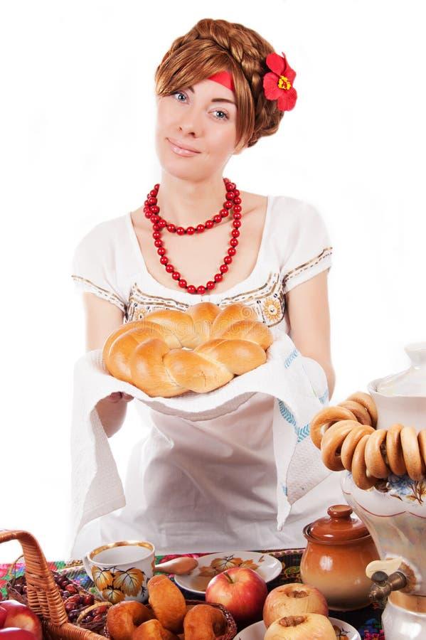 提供传统大面包的好客的俄国妇女 免版税库存图片