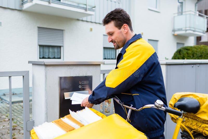 提供信件的邮差到接收者邮箱  免版税库存照片