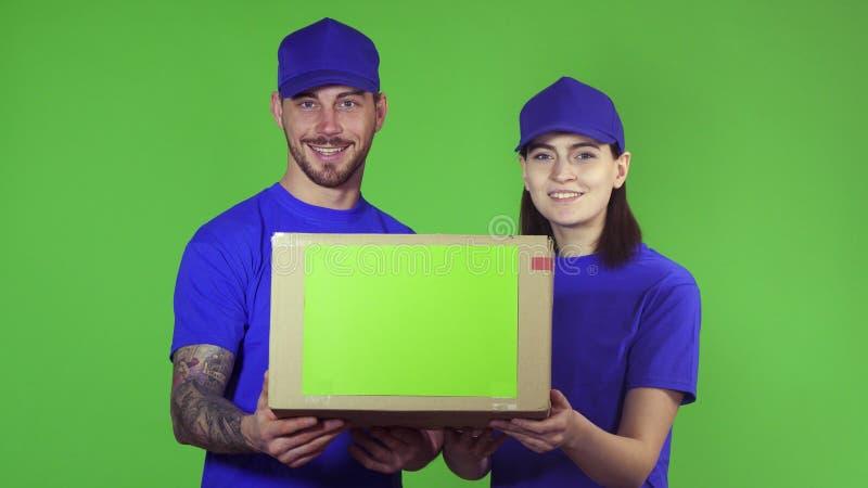 提供包裹箱子的两名愉快的专业交付工作者对照相机 库存图片