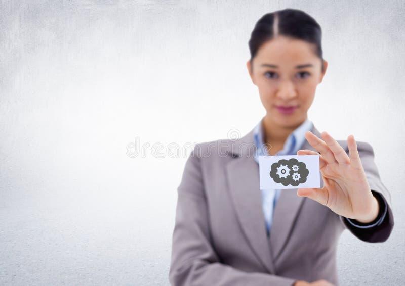 提供卡片的女商人显示灰色云彩和齿轮图表对白色墙壁 库存照片