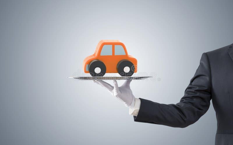 提供在银色盘子的商人橙色汽车 库存照片