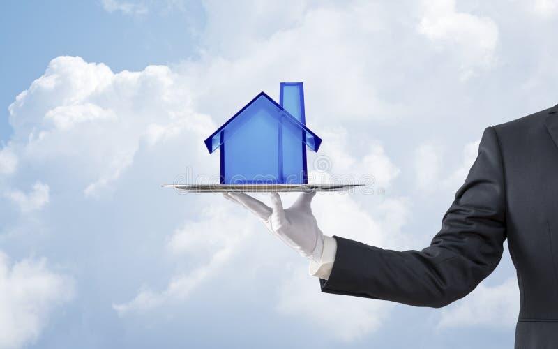 提供在银色盘子的商人蓝色水晶房子模型 库存图片